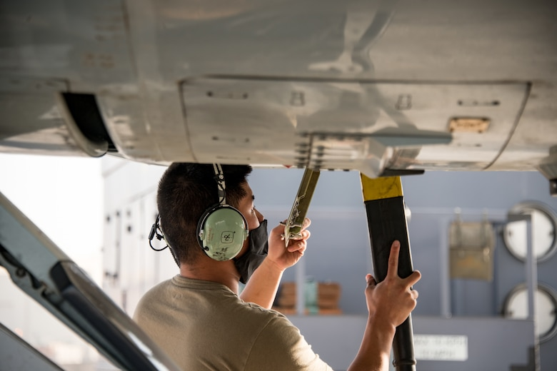 A man plugs in a power cord to an RC-135 Rivet Joint aircraft