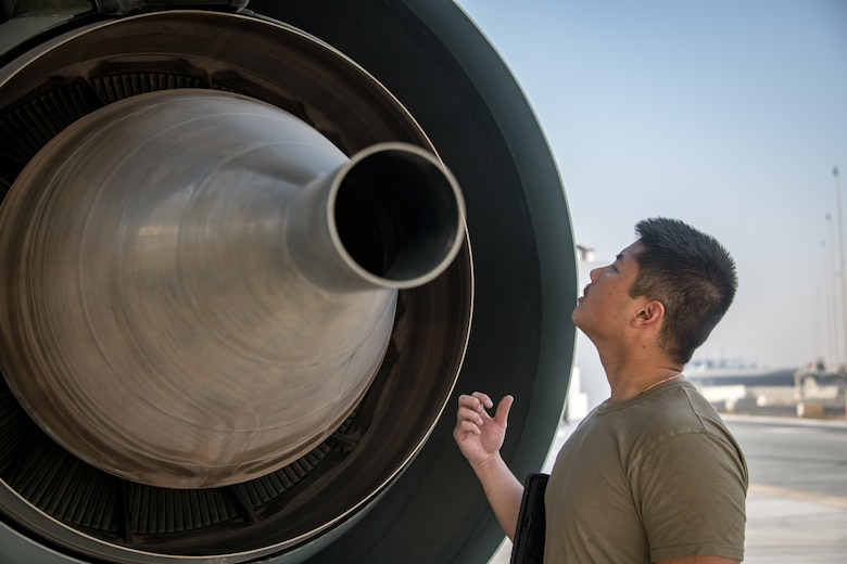 A man inspects the engine of an RC-135 Rivet Joint aircraft
