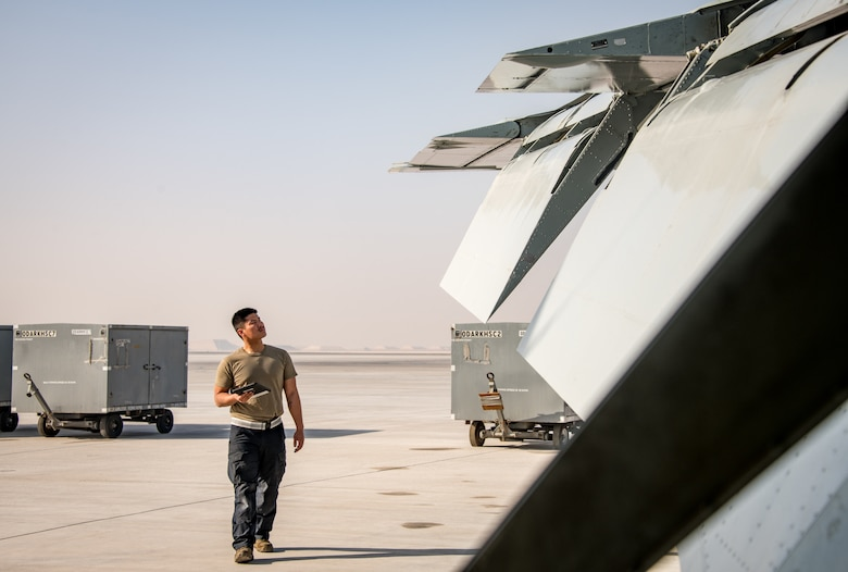 A man inspects the wing of an aircraft on a flightline