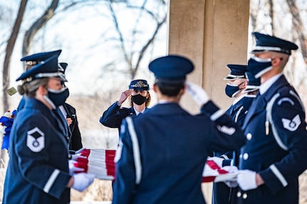 U.S. Air Force Col. Erica Rabe, Joint Base Anacostia-Bolling and 11th Wing vice commander,  salutes as the United States Air Force Honor Guard Pallbearers fold a flag as part of modified military funeral honors with funeral escort for U.S. Air Force Lt. Col. Bruce Burns in Section 82 of Arlington National Cemetery, Arlington, Virginia, March 22, 2021. Burns served in the Air Force from 1962 to 1982. His spouse, Janet Burns, received the flag from his service. The funeral was an historic occasion for the United States Honor Guard, with the largest female presence on a pallbearers team in Air Force history. (U.S. Army photo by Elizabeth Fraser)