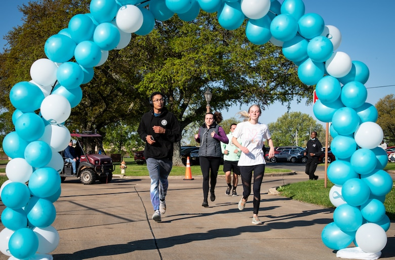 Participants in the Sexual Assault Awareness Month 5K run through the finish line at Barksdale Air Force Base, Louisiana, April 2, 2021.