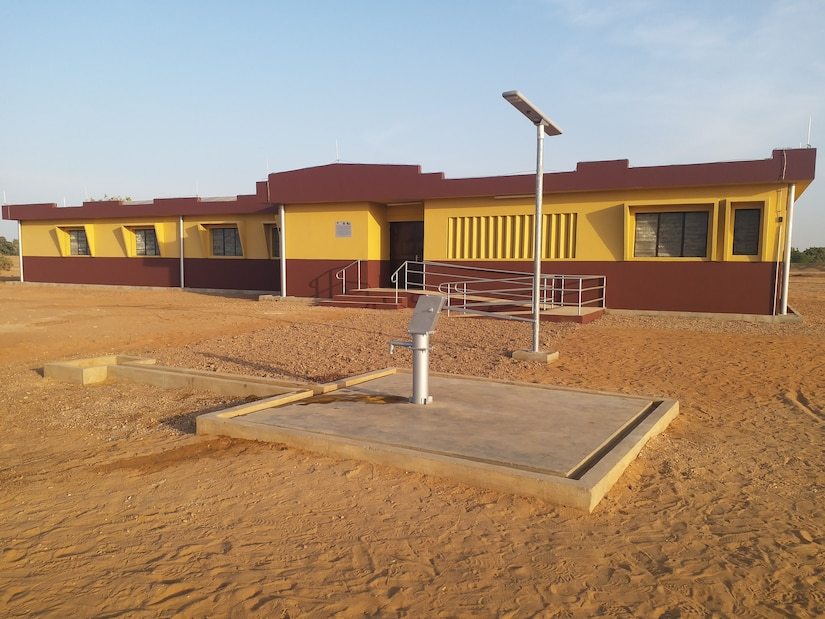 A recently completed health clinic, with a water well hand pump on a concrete pad and a solar powered light pole seen in the foreground, is seen here in the remote village of Money in Benin in Africa. The clinic and various associated facilities also built comprise one of two similar clinic projects recently completed by the U.S. Army Corps of Engineers in that region of Benin through funding from AFRICOM and coordinated closely with the U.S. State Department.