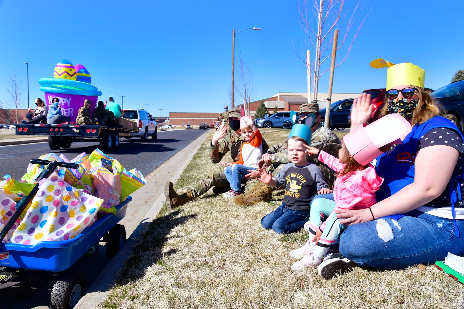 """Families waving as the """"Operation Bunny Trail"""" Easter parade rolls through military family housing."""