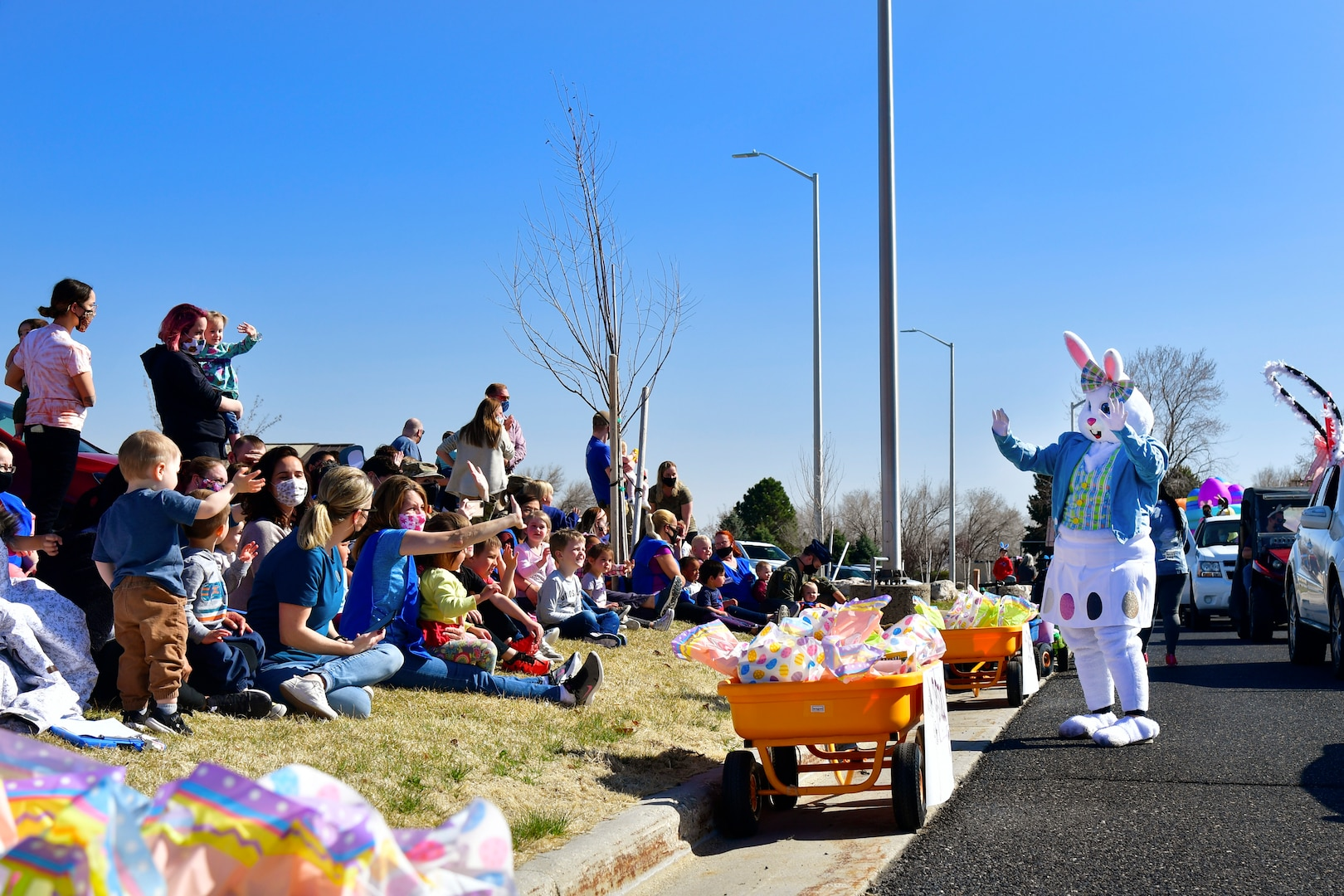 """The Easter Bunny waves to families during the """"Operation Bunny Trail"""" Easter parade in military family housing."""