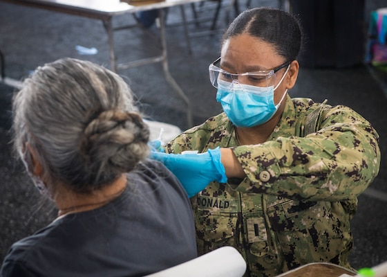 Lt. j.g. Tomeka McDonald administers a COVID-19 vaccination at a community vaccination center in Jacksonville, Florida.