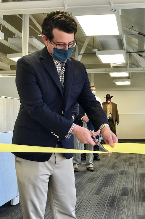 Mark Sinder, Commander, Navy Installations Command's (CNIC) operations director, cuts a ribbon for the the official opening of the Navy Public Safety Systems Office at CNIC Headquarters onboard the Washington Navy Yard, D.C., March 29.