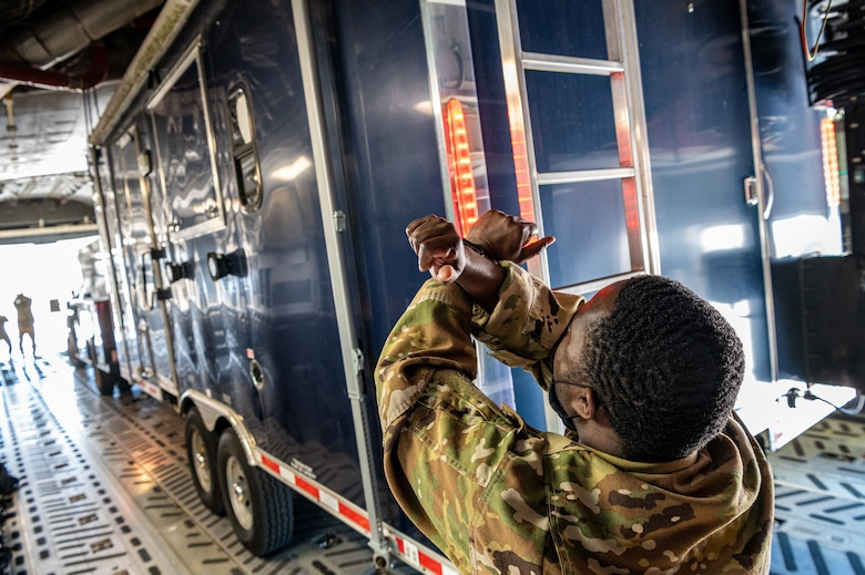 Staff Sgt. John Shauri, 3rd Airlift Squadron loadmaster, marshals a Delaware Army National Guard trailer onto a C-17 Globemaster III during joint training at Dover Air Force Base, Delaware, March 29, 2021. The training focused on providing rapid global airlift through the integration of U.S. Air Force Airmen and Delaware National Guard Soldiers. (U.S. Air Force photo by Senior Airman Christopher Quail)