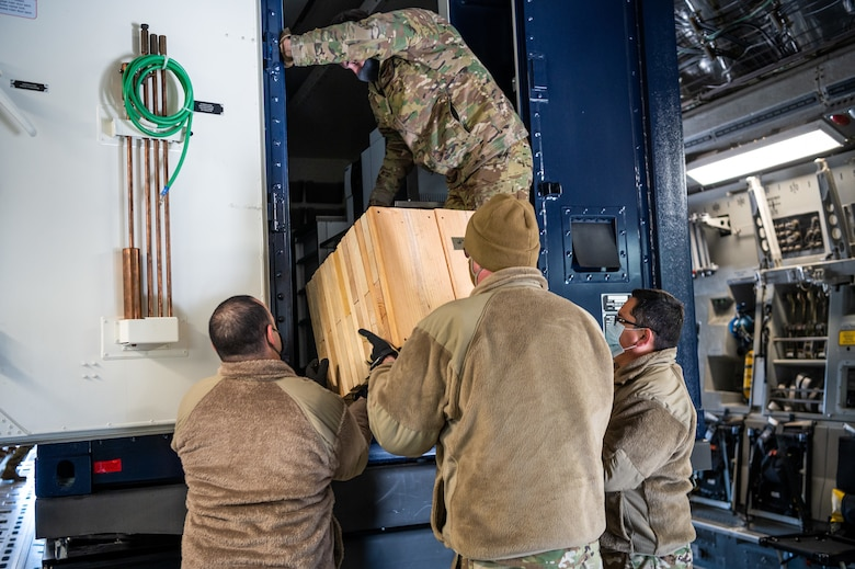 Airmen from the 3rd Airlift Squadron and Soldiers from the 31st Civil Support Squadron, Delaware Army National Guard, unload wood shoring during joint training at Dover Air Force Base, Delaware, March 29, 2021. The training focused on providing rapid global airlift through the integration of U.S. Air Force Airmen and Delaware National Guard Soldiers. (U.S. Air Force photo by Senior Airman Christopher Quail)