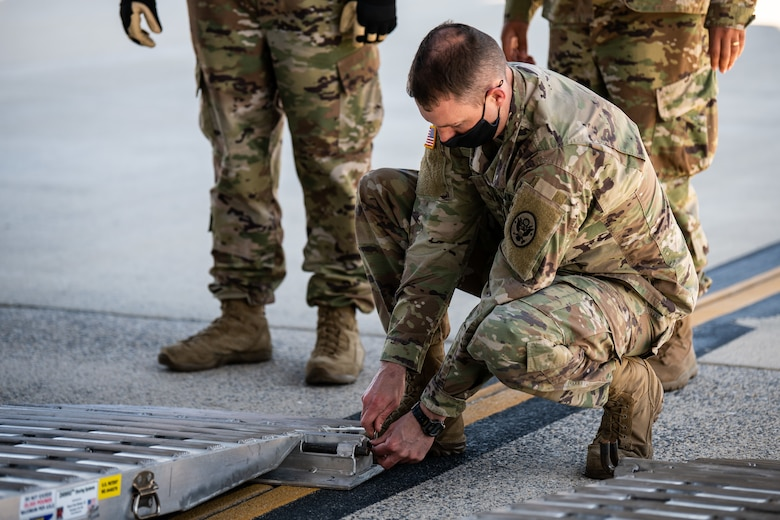 U.S. Army Capt. Dan Collins, 31st Civil Support Squadron, Delaware Army National Guard science officer, places shoring at the ramp of a C-17 Globemaster III during joint training at Dover Air Force Base, Delaware, March 29, 2021. The training focused on providing rapid global airlift through the integration of U.S. Air Force Airmen and Delaware National Guard Soldiers. (U.S. Air Force photo by Senior Airman Christopher Quail)