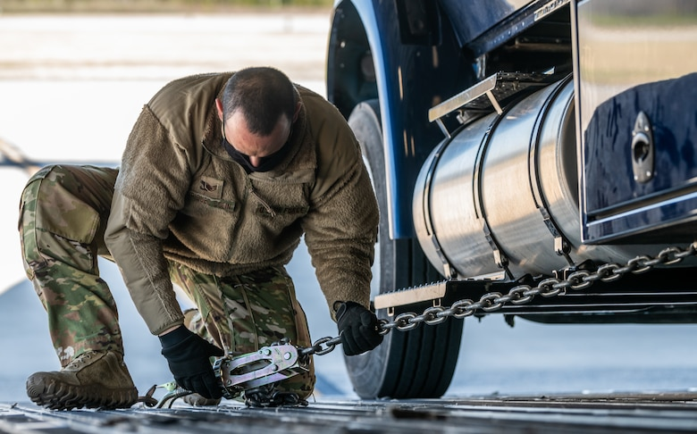 Staff Sgt. Jonathan Enriquez Colin, 3rd Airlift Squadron loadmaster, ties down a Delaware Army National Guard truck onto a C-17 Globemaster III during joint training at Dover Air Force Base, Delaware, March 29, 2021. The training focused on providing rapid global airlift through the integration of U.S. Air Force Airmen and Delaware National Guard Soldiers. (U.S. Air Force photo by Senior Airman Christopher Quail)