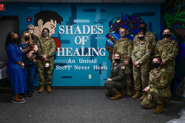 a group of people pose for a photo in front of a teal mural