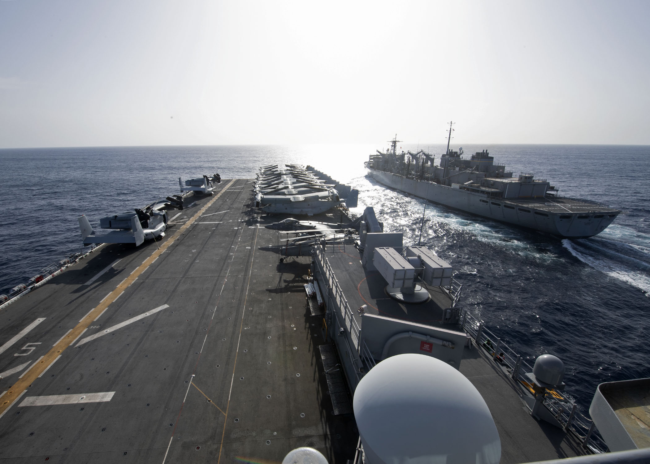 USS Iwo Jima (LHD 7), left, approaches the fast combat support ship USNS Supply (T-AOE 6) during a replenishment-at-sea, April 3, 2021.