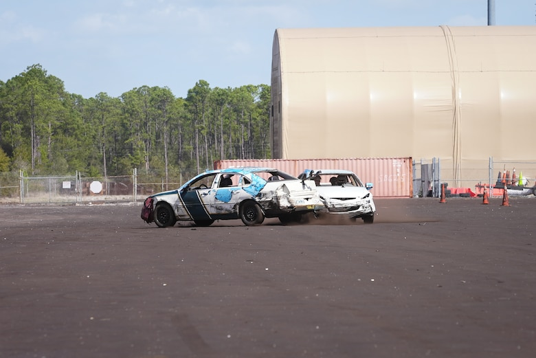 Two cars kick up dust off of runway as they collide.