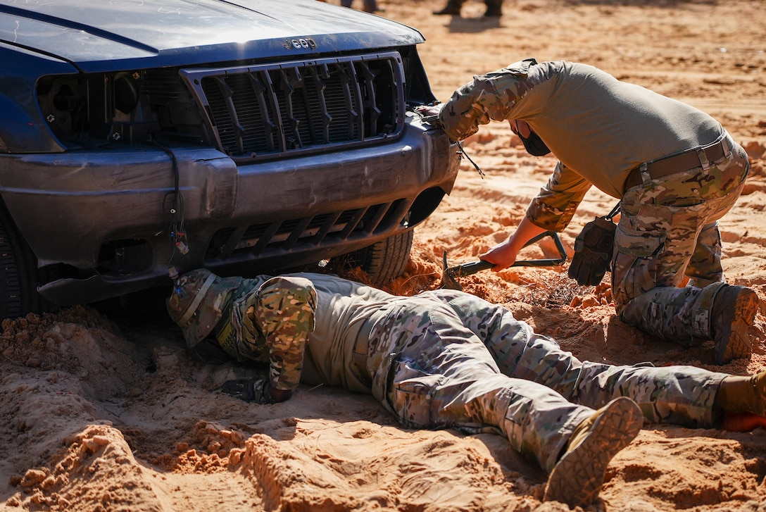 Airmen in the dirt with shovels dig underneath car.