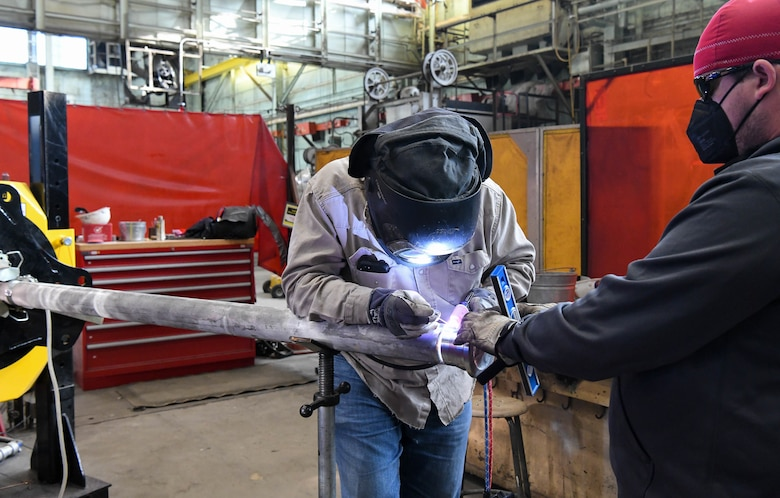 Dustin Williams, right, a pipefitter, holds a flange in place as fellow pipefitter Billy Joe Emberton places tack welds, March 4, 2021, at the Model Shop at Arnold Air Force Base, Tenn. April is National Welding Month. (U.S. Air Force photo by Jill Pickett)