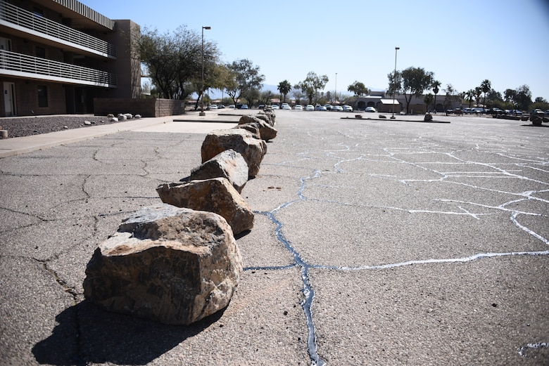 A line of boulders sit in font of a building.