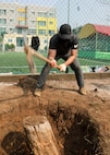 U.S. Marine Corps Sgt. Robert Perez, a chemical, biological, radiological, and nuclear specialist with U.S. Marine Corps Forces – Korea, removes a tree stump during a volunteer event at Sunrin Orphanage, Pohang, South Korea, March 13, 2021.