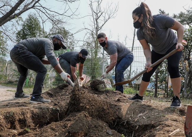 U.S. Marines with U.S. Marine Corps Forces – Korea fill in the holes created from removed tree stumps during a volunteer event at Sunrin Orphanage, Pohang, South Korea, March 13, 2021.