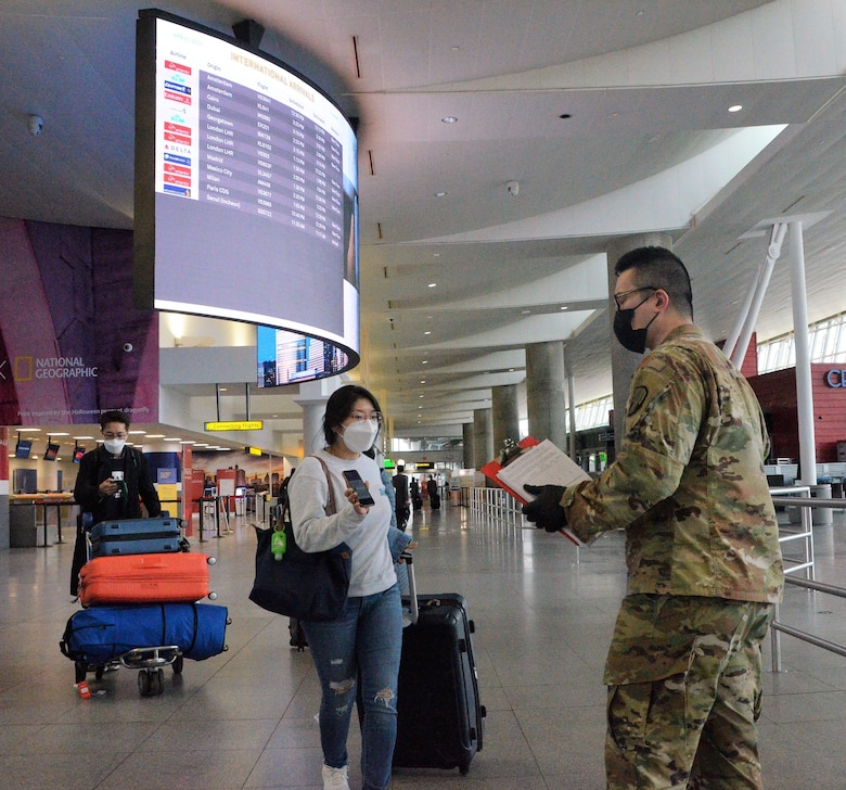 New York Army National Guard Spc. Enda Wang, a member of the 187th Signal Company, checks the phone of an international traveler arriving at John F Kennedy International Airport, New York, to ensure she completed the digital version of the New York State Travel Health form April 1, 2021. Between October 16 and April 1, New York National Guard personnel checked and collected over 3 million electronic and paper forms.