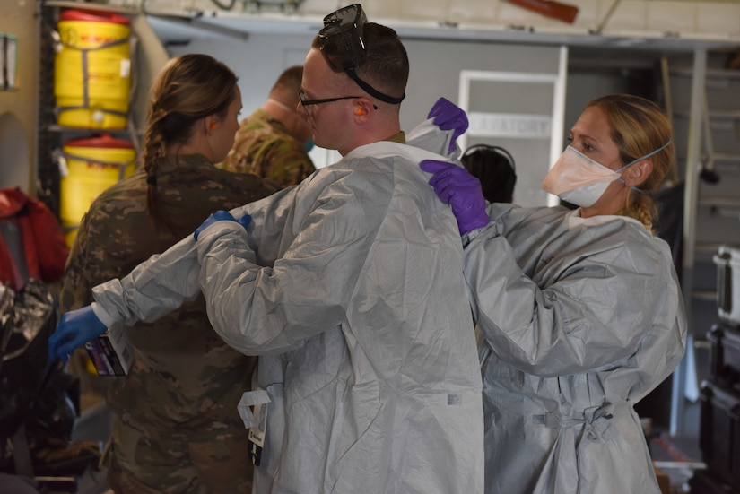 U.S. Air Force Airmen from the 775th Expeditionary Aeromedical Evacuation flight from Travis Air Force Base, California, don personal protective equipment aboard a C-17 Globemaster III on Joint Base Lewis-McChord, Washington, March 31, 2021. Aeromedical evacuation personnel are responsible for caring for medical patients in-flight and preparing a safe environment for them as well as the aircrew. (U.S. Air Force photo by Senior Airman Mikayla Heineck)
