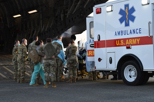 A COVID-19 patient who was being cared for at Madigan Army Medical Center is loaded onto a C-17 Globemaster III by an aeromedical evacuation team from the 775th Expeditionary Aeromedical Evacuation flight from Travis Air Force Base, California, and other medical professionals from Madigan, at Joint Base Lewis-McChord, Washington, March 31, 2021. The patient was in severe respiratory distress and was hooked up to an extracorporeal membrane oxygenation (EMCO) system, which aids the body in breathing. (U.S. Air Force photo by Senior Airman Mikayla Heineck)