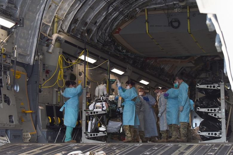 A COVID-19 patient who was being cared for at Madigan Army Medical Center, is loaded onto a C-17 Globemaster III by an aeromedical evacuation team from the 775th Expeditionary Aeromedical Evacuation flight from Travis Air Force Base, California, and other medical professionals from Madigan, at Joint Base Lewis-McChord, Washington, March 31, 2021. The patient was in severe respiratory distress and was hooked up to an extracorporeal membrane oxygenation (EMCO) system, which aids the body in breathing. (U.S. Air Force photo by Senior Airman Mikayla Heineck)