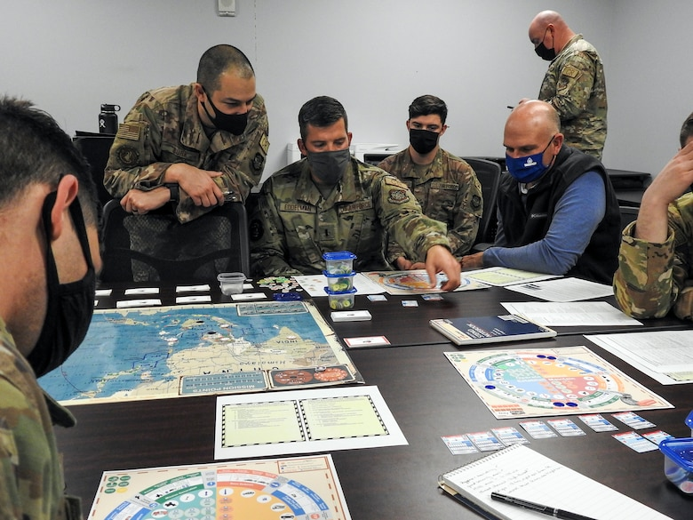 """Airmen from various units within the 621st Contingency Response Wing play a prototype military strategy game March 25, 2021, at Travis Air Force Base, California. The game, called """"Kingfish ACE"""" focuses on a hypothetical situation in the Western Pacific and is a strategy game similar to """"Risk"""" and """"Dungeons & Dragons."""" (U.S. Air Force photo by Senior Airman Chad Kotce)"""
