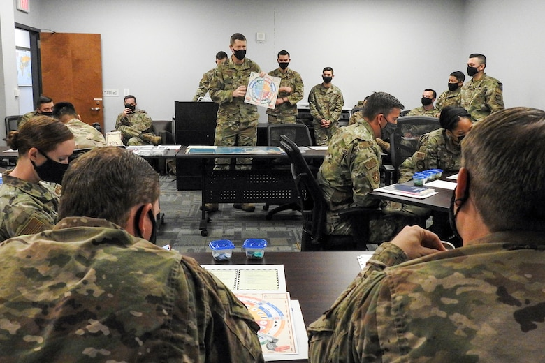"Twenty-five Airmen from various units within the 621st Contingency Response Wing listen to instructions on how to play a prototype board game called ""Kingfish ACE"" March 26, 2021, at Travis Air Force Base, California. U.S. Air Force Lt. Col. Troy Pierce, while attending the Marine Corps War College, created the game as part of his final project at the college. (U.S. Air Force photo by Senior Airman Chad Kotce)"