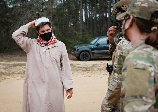Two Airmen speak to a man wearing a tunic.