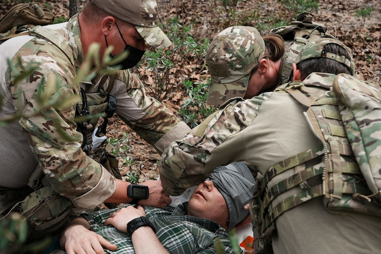 Three Airmen provide medical care to a casualty.