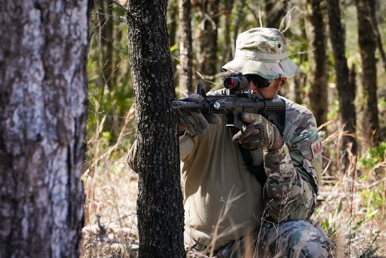A kneeling Airman aims a weapon around a tree.