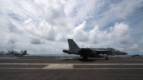 """An F/A-18E Super Hornet, assigned to the """"Blue Diamonds"""" of Strike Fighter Squadron (VFA) 146, lands on the flight deck of the aircraft carrier USS Theodore Roosevelt (CVN 71) April 5, 2021."""