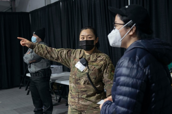 Senior Airman Can Liu, from Queens, N.Y., and a 335th Expeditionary Medical Operations Squadron general purpose Airman, ushers a community member at the state-led, federally-supported Medgar Evers College Community Vaccination Center in Brooklyn, N.Y., March 24, 2021. Liu, who is deployed from the 20th Civil Engineer Squadron out of Tyndall Air Force Base, Fla., was born in Fushun, China, is fluent in Mandarin. Liu is able to translate for Chinese community members who have questions while receiving their COVID-19 vaccination. U.S. Northern Command, through U.S. Army North, remains committed to providing continued, flexible DoD support to the Federal Emergency Management Agency as part of the whole-of-government response to COVID-19. (U.S. Air Force photo by Tech. Sgt. Ashley Nicole Taylor)