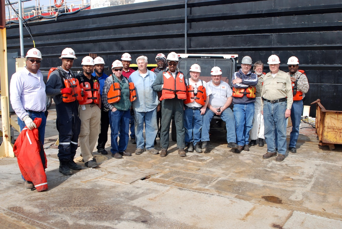 Heavy Mobile Equipment Mechanic Leader Robert Woods (center) and crew prepares for a safety meeting preceding the undocking of Revetment Mooring Barge 7401. (USACE photo by Brenda Beasley)