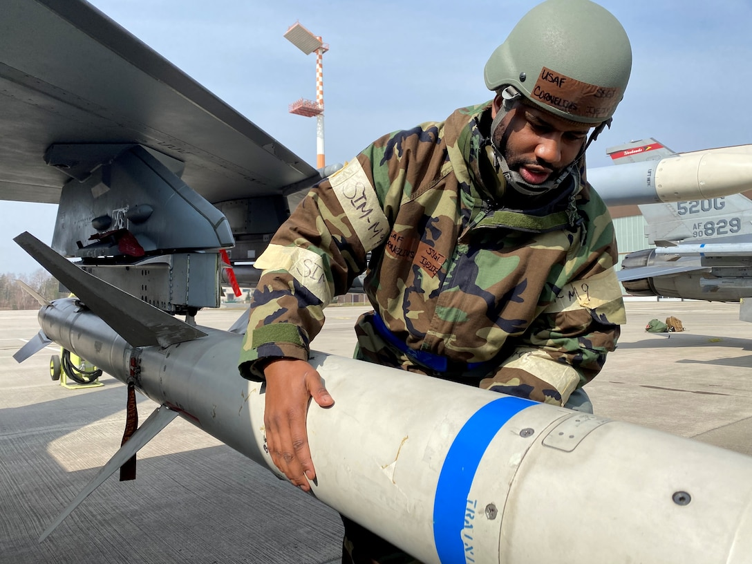 U.S. Air Force Staff Sgt. Cornelius Ijezie, a 52nd Maintenance Squadron Munitions Stockpile Supervisor, inspects a munition on an U.S. Air Force F-16 Fighting Falcon, while in Mission Oriented Protective Posture gear during an ACE exercise at Ramstein Air Base Germany, March 25, 2021. ACE, is Agile Combat Employment, an operational concept that allows forces to generate sorties from various locations with the support of multi-capable Airmen. (U.S. Air Force photo by Tech Sgt. Warren Spearman Jr.)