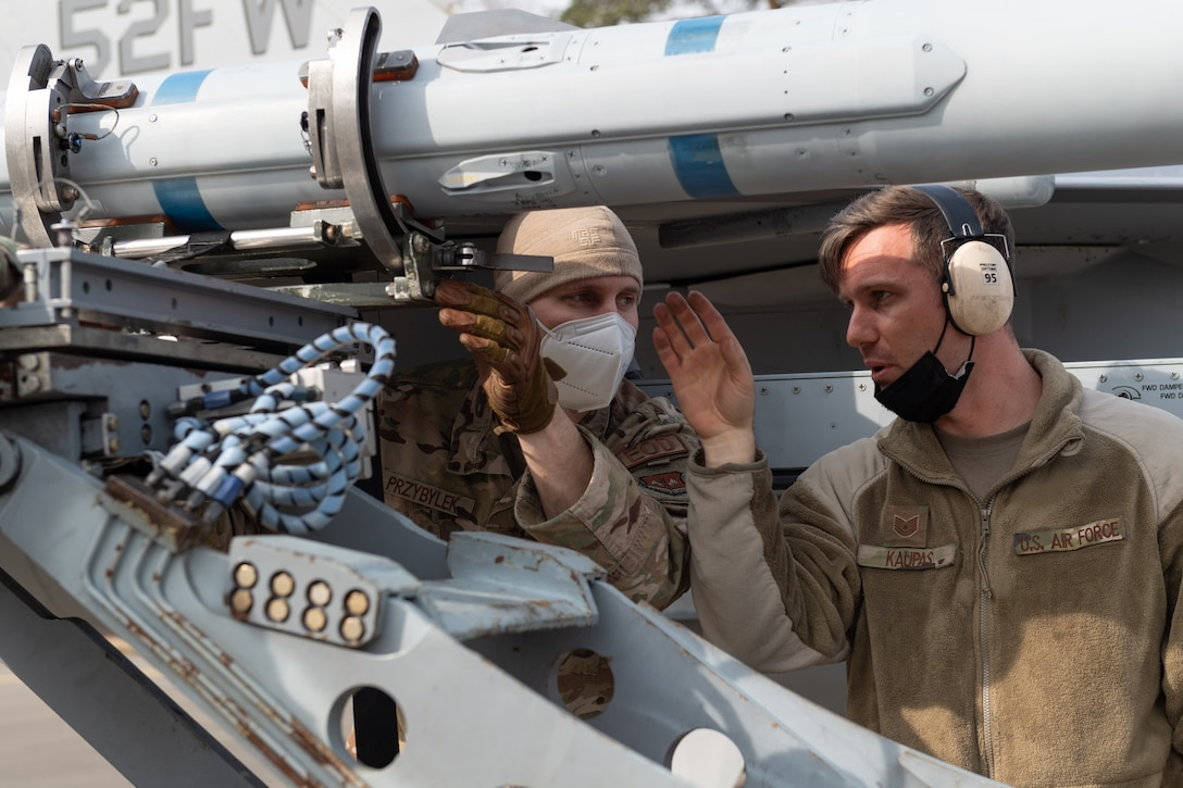 U.S. Air Force Tech. Sgt. Joseph Kaupas (right), 52nd Aircraft Maintenance Squadron Weapons Expediter instructs U.S. Air Force Staff Sgt. Thomas Przybylek, 52nd Explosive Ordnance Disposal technician (left), how to place a munition on an U.S. Air Force F-16 Fighting Falcon at an Agile Combat Employment exercise at Ramstein Air Base Germany, March 25, 2021. The exercise called for Spangdahlem Airmen to support operations in a simulated adverse environment with minimal personnel, resources and time. (U.S. Air Force photo by Senior Airman John Wright)