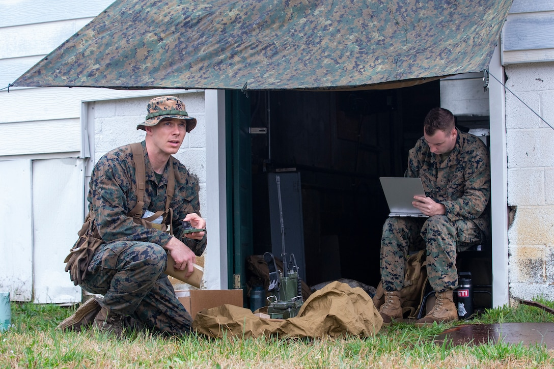 U.S. Marine Corps Sgt. Mitchell Firgens, a radio supervisor with Communication Company, Headquarters Battalion, 2d Marine Division, right, and Capt. Travis Bird, an infantry officer with 1st Battalion, 6th Marine Regiment, 2d Marine Division, conducts a notional call for fire on an enemy position during a Division Leaders Assessment Program (DLAP) at Fort Pickett, V.A., March 28, 2021. The program prepares Marine Corps captains with the ability, proficiency and skills of becoming infantry company commanders. This is a pilot iteration to refine the schedule of events, processes and procedures that will be used to evaluate inbound infantry captains for company command. (U.S. Marine Corps photo by Pfc. Sarah Pysher)