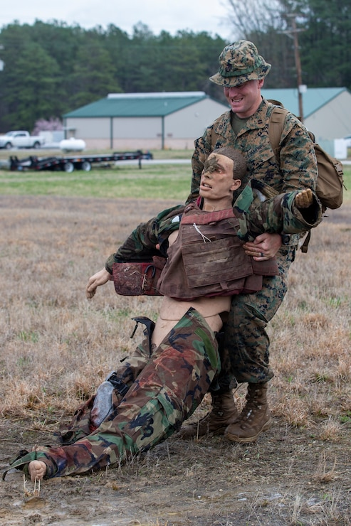 U.S. Marine Corps Capt. Matthew McGowan, an infantry officer with Headquarters Company, 6th Marine Regiment, 2d Marine Division, buddy drags a mannequin during a Division Leaders Assessment Program (DLAP) at Fort Pickett, V.A., March 28, 2021. The program prepares Marine Corps captains with the ability, proficiency and skills of becoming infantry company commanders. This is a pilot iteration to refine the schedule of events, processes and procedures that will be used to evaluate inbound infantry captains for company command. (U.S. Marine Corps photo by Pfc. Sarah Pysher)