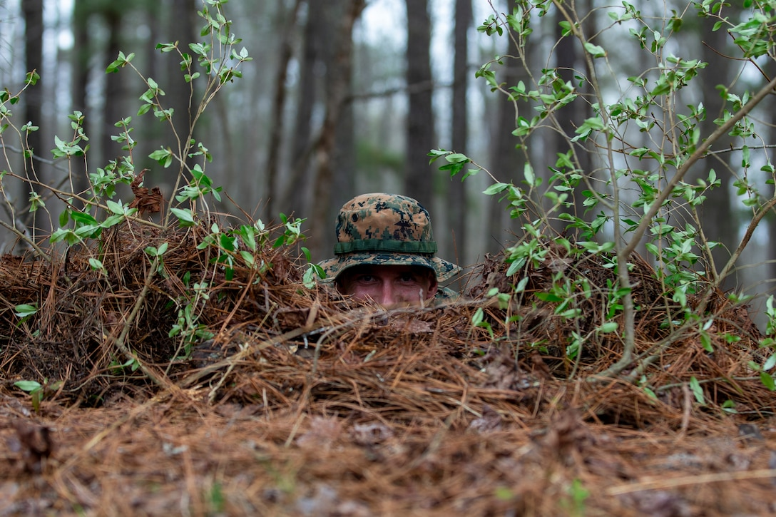 U.S. Marine Corps Capt. Travis Bird, an infantry officer with 1st Battalion, 6th Marine Regiment, 2d Marine Division, lays in a fighting position during a Division Leaders Assessment Program (DLAP) at Fort Pickett, V.A., March 28, 2021.