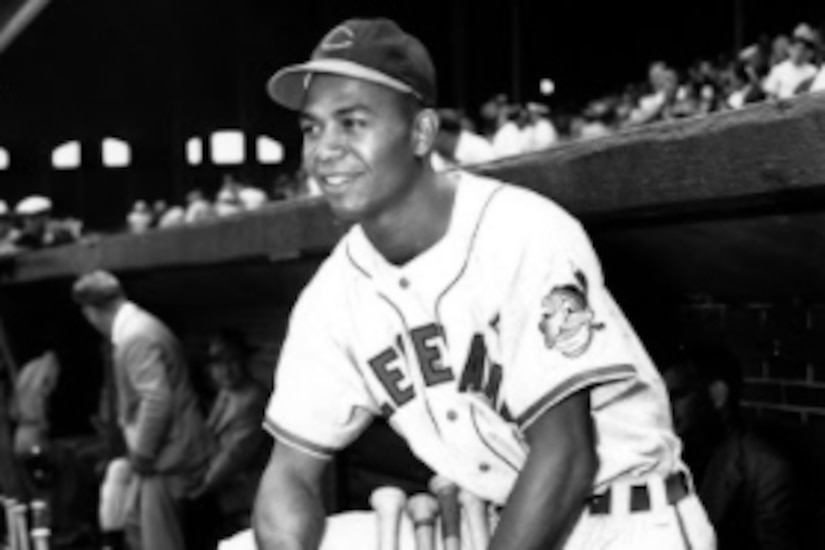A baseball player poses for a photo at the edge of the dugout.