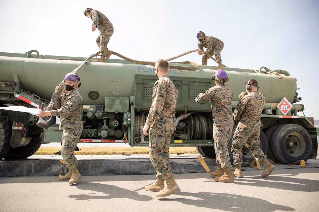 Marines unravel a hose from a truck.