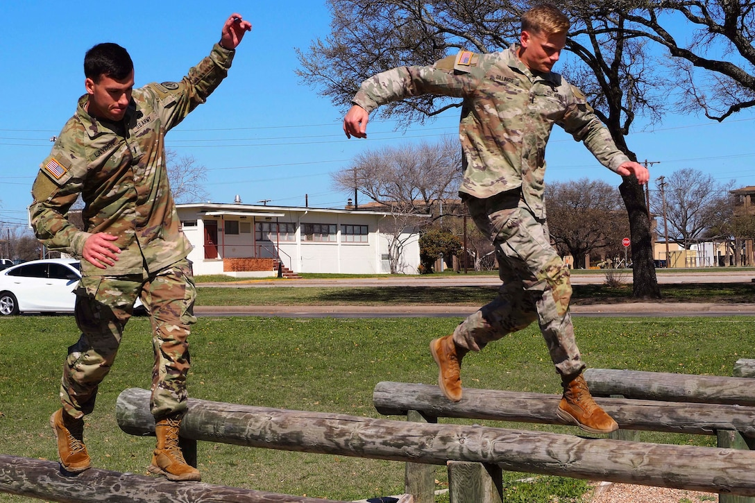Two airmen run on logs.