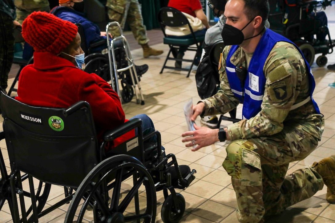 A soldier kneels next to a women in a wheelchair.