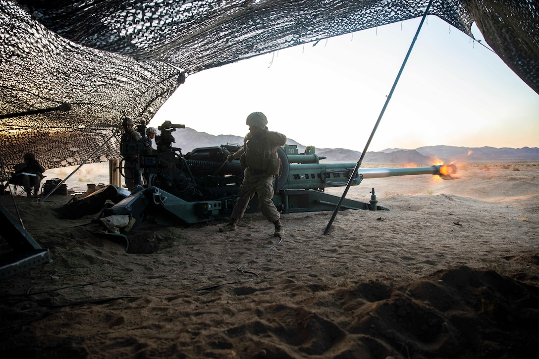 A Marine fires a tank in desert under a netted tent.