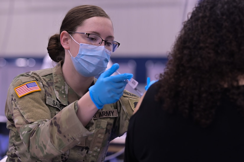 Illinois Army National Guard Spc. Emily Salmon, 2123 Forward Support Company combat medic, administers the COVID-19 vaccine in the South Suburban College gym, South Holland, Illinois, Feb. 25, 2021. Guard members were called on to support COVID-19 relief efforts.