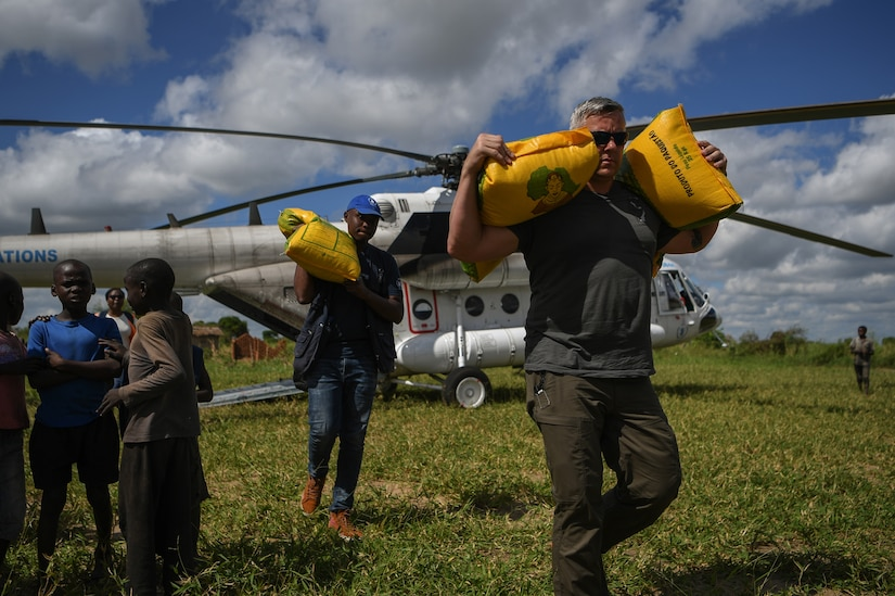 Troops offload relief supplies from a helicopter.