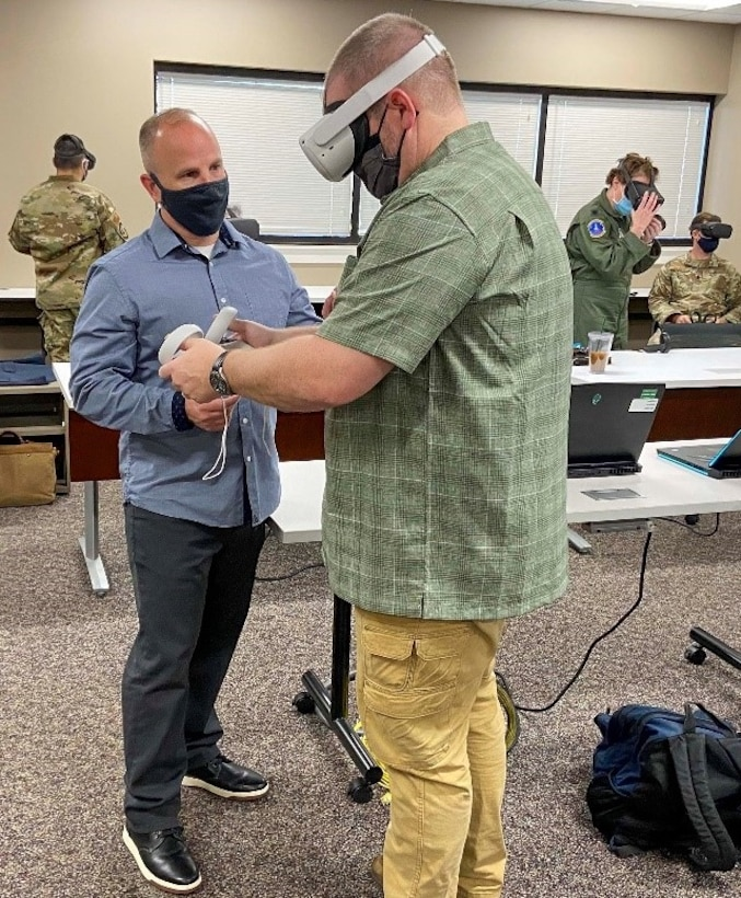 Dr. Andy Clayton, an assistant professor of leadership and augmented reality/virtual reality research task force director, helps a Regional Security Studies student during a VR trip to South America at Maxwell Air Force Base, Alabama, Mar. 29, 2021. This type of immersive learning helps students retain information from their VR experience and allows them to interact with curriculum content.