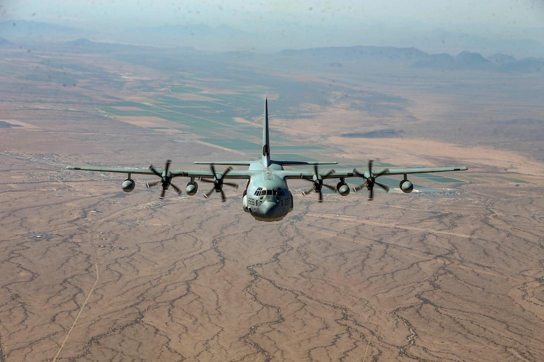 An aircraft flies over dusty terrain.