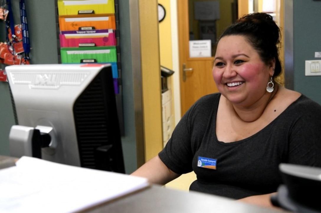 A woman sits at a computer.
