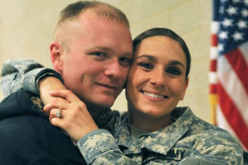 A woman in a military uniform puts her arms around the neck of a man.